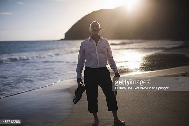 Portrait of retired businessman at coast, holding shoes and tie