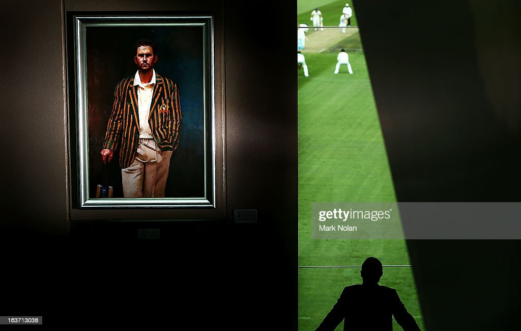 A portrait of <a gi-track='captionPersonalityLinkClicked' href=/galleries/search?phrase=Ricky+Ponting&family=editorial&specificpeople=176564 ng-click='$event.stopPropagation()'>Ricky Ponting</a> is displayed in the foyer of the Tasmanian Cricket Museum as a man watches play during day two of the Sheffield Shield match between the Tasmania Tigers and the Victoria Bushrangers at Blundstone Arena on March 15, 2013 in Hobart, Australia.
