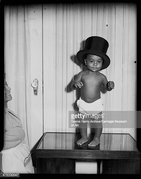 Portrait of Robert E Williams Jr in diaper and top hat standing on table in front of curtain with mother Alberta Russell Williams on left Pittsburgh...