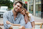 Portrait of romantic couple sitting at sidewalk cafe in city