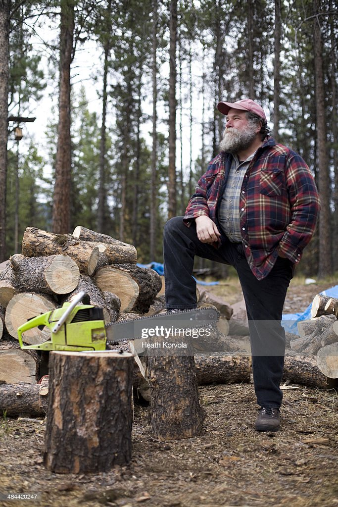Portrait of rural man, chainsaw and wood pile.