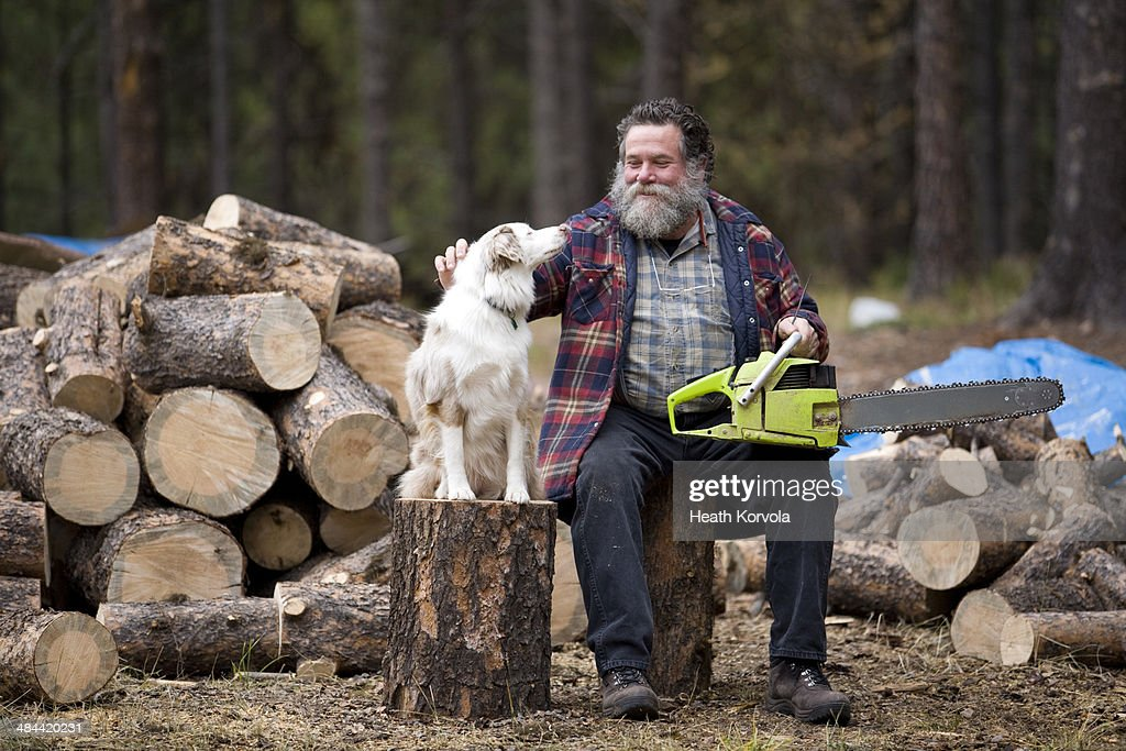 Portrait of rural man, dog and wood pile.