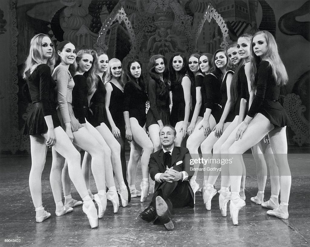 Portrait of Russian-born American ballet director and choreographer George Balanchine (1904-1983), artistic director of the New York City Ballet, who sits with his legs crosed on a stage surrounded female dancers, 1969.