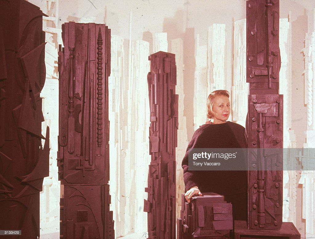 Portrait of Russianborn American sculptor Louise Nevelson poses with several of her works 1950s