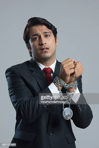 Portrait of sad businessman tied in chain against gray background