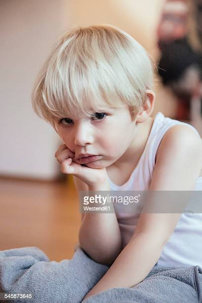 Portrait of sad little boy with head in his hand