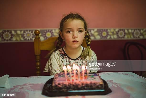 Portrait of sad little girl with birthday cake
