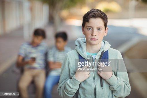 Portrait of sad schoolboy with schoolbag standing in campus : Stock Photo