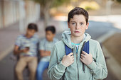 Portrait of sad schoolboy with schoolbag standing in campus at school