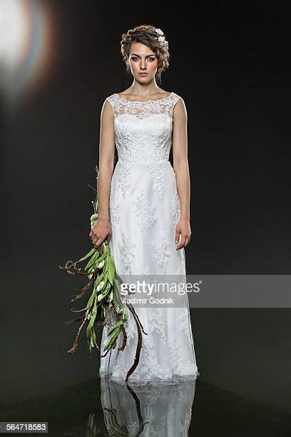 Portrait of sad young bride holding wilted bouquet while standing in water against gray background