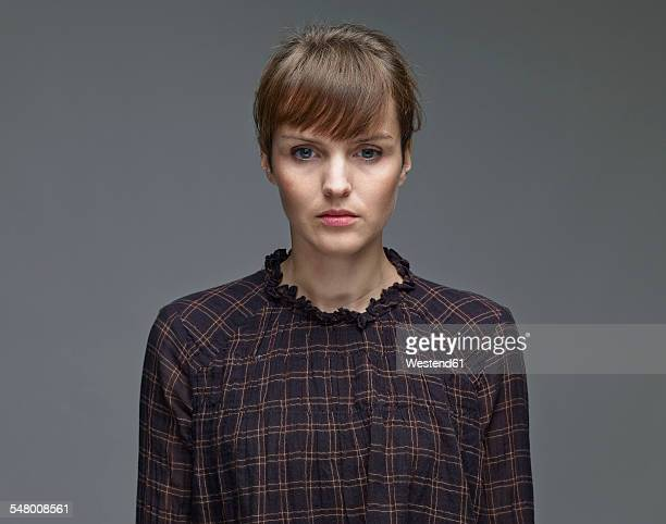 Portrait of sad young woman in front of grey background