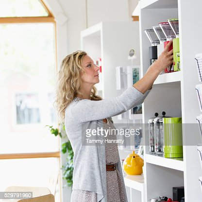 Portrait of sales clerk putting products on shelf : Stock-Foto