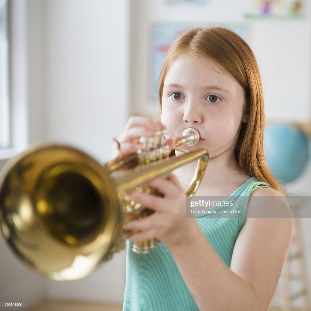 Portrait of school girl (8-9) playing trumpet during music class