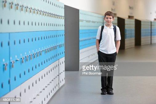 Portrait of schoolboy with hands in pockets in school corridor