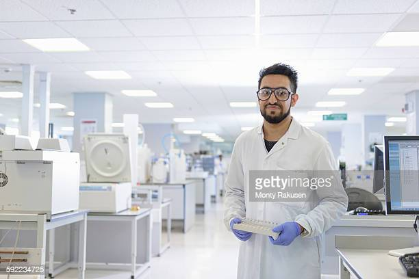 Portrait of scientist with analyst samples in testing laboratory