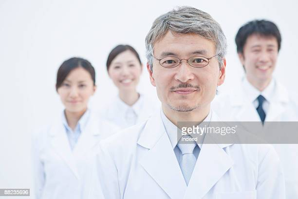 Portrait of scientists, people in background
