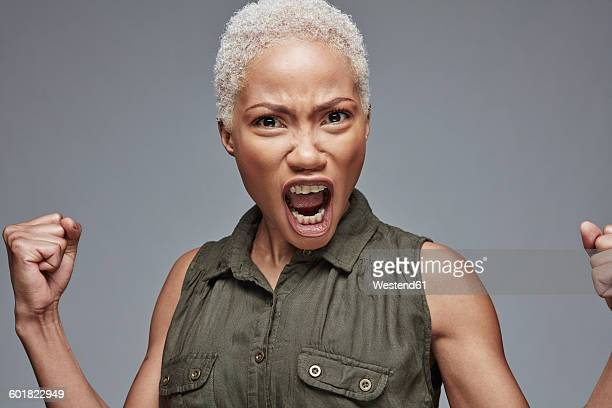 Portrait of screaming woman in front of grey background