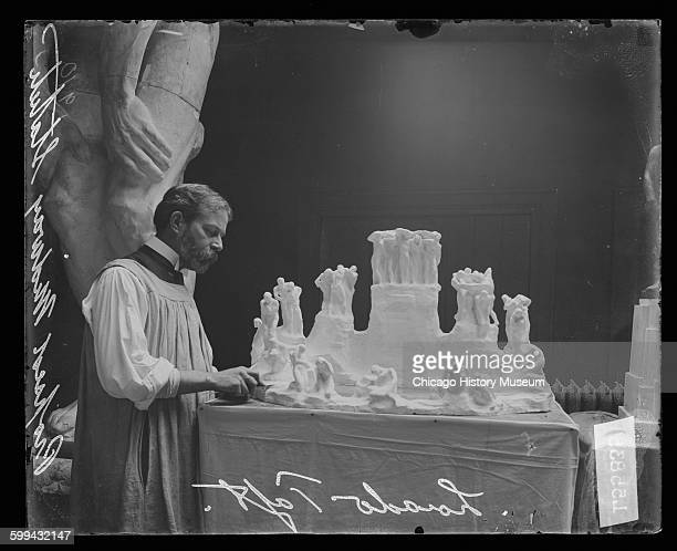 Portrait of sculptor Lorado Taft working on a small model of his proposed Midway statue the Fountain of Creation in a room Chicago Illinois 1910 The...