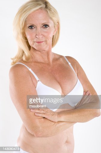 portrait of semi nude mature woman with arms crossed stock