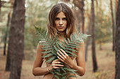 Wild woman. Portrait of seminude girl with Fern