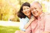 Portrait Of Senior Asian Couple Sitting In Park Together Smiling To Camera