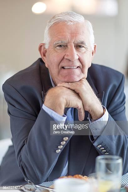 Portrait of senior businessman having breakfast in hotel restaurant