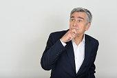 Portrait of Caucasian senior businessman thinking horizontal studio shot