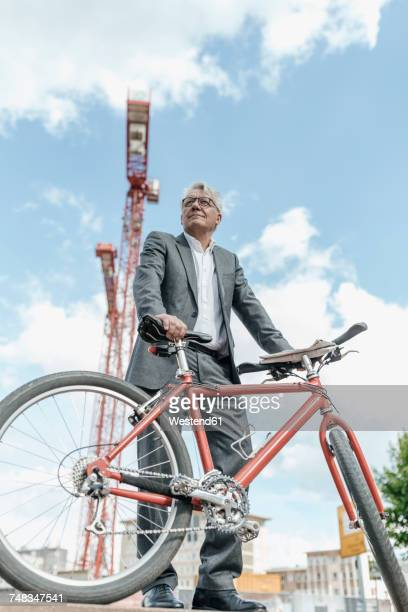 Portrait of senior businessman with bicycle in front of construction crane
