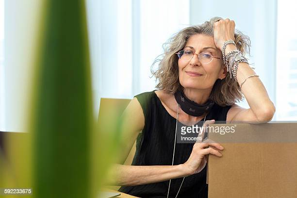 Portrait of senior businesswoman relaxing on office chair