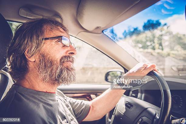 Portrait of Senior caucasian Man with Glasse and Beard Driving