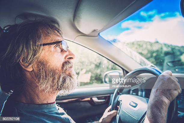 Portrait of Senior Caucasian Man with Glasses and Beard Driving