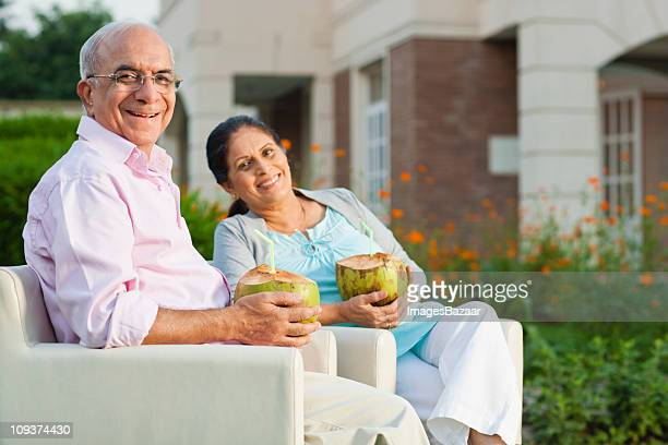 Portrait of senior couple holding coconuts in garden