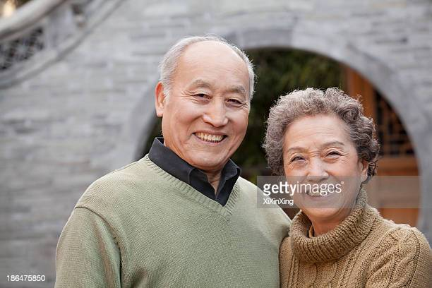 Portrait of senior couple in front of round arch, Beijing