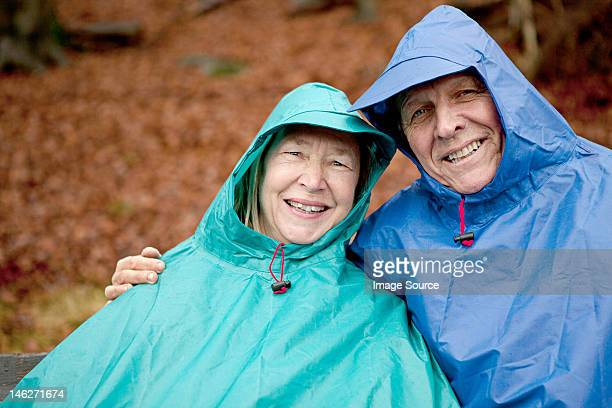 Portrait of senior couple sitting on park bench wearing waterproofs