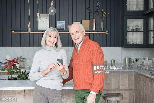Portrait de couple Senior souriant dans cuisine avec un smartphone
