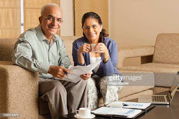 Portrait of senior couple working in living room, with laptop on coffee table