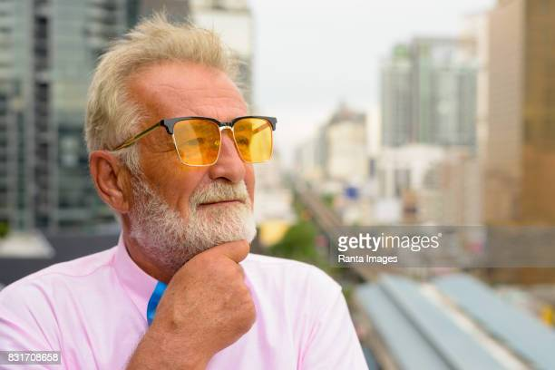 Portrait of senior handsome man wearing stylish clothes against view of the city in Bangkok Thailand