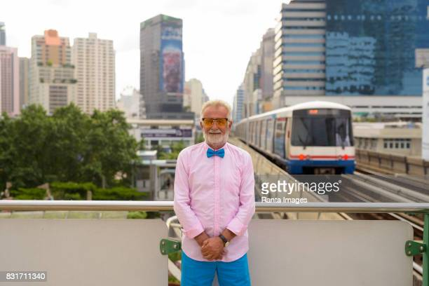 Portrait of senior handsome man wearing stylish clothes against view of the city and BTS sky train station in Bangkok Thailand