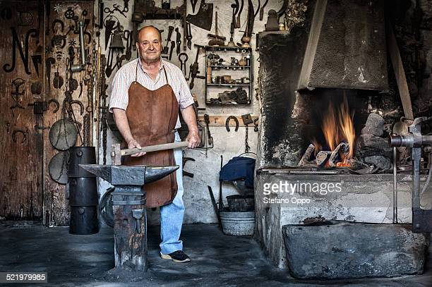 Portrait of senior male blacksmith in traditional workshop, Cagliari, Sardinia, Italy