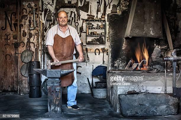 Portrait of senior male blacksmith in traditional workshop, Cagliari, Sardinia, Italy