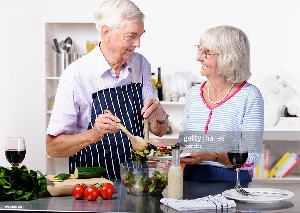 Portrait Of Senior Man Dishing Salad : Stock Photo