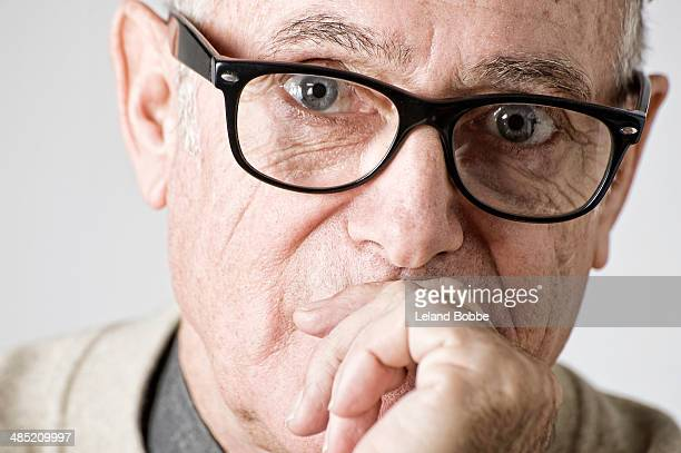 Portrait of senior man, hand on mouth