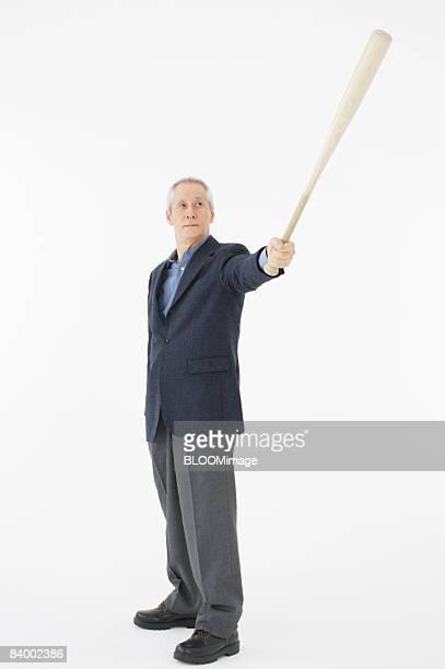 Portrait of senior man holding baseball bat, studio shot