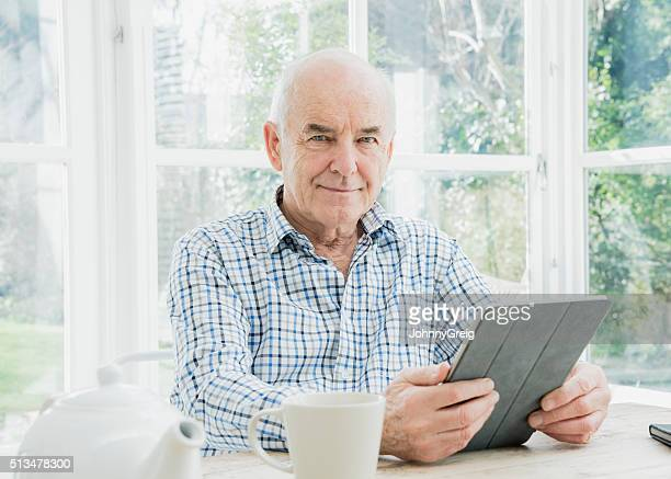 Portrait of senior man holding digital tablet looking at camera