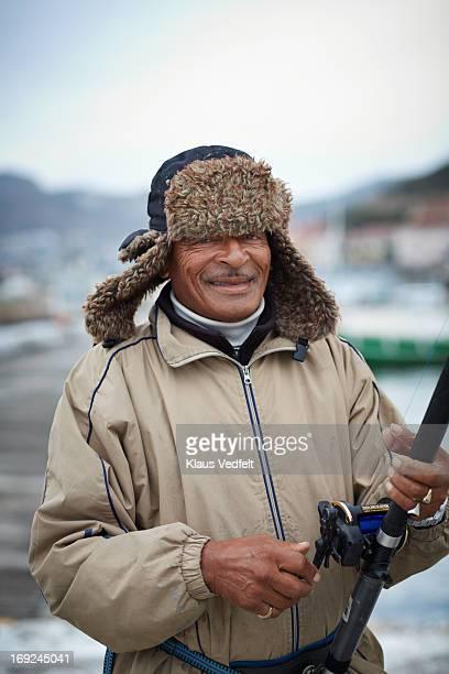 Portrait of senior man holding fishing rod