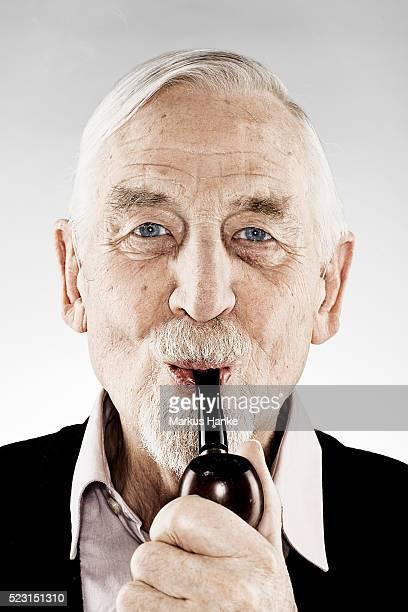 Portrait of senior man holding pipe