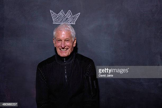 Portrait of senior man in front of chalked crown on blackboard