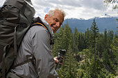 Portrait of senior man in mountains carrying backpack, looking over shoulder