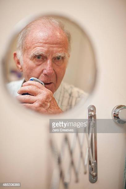 Portrait of senior man in shaving mirror using electric razor