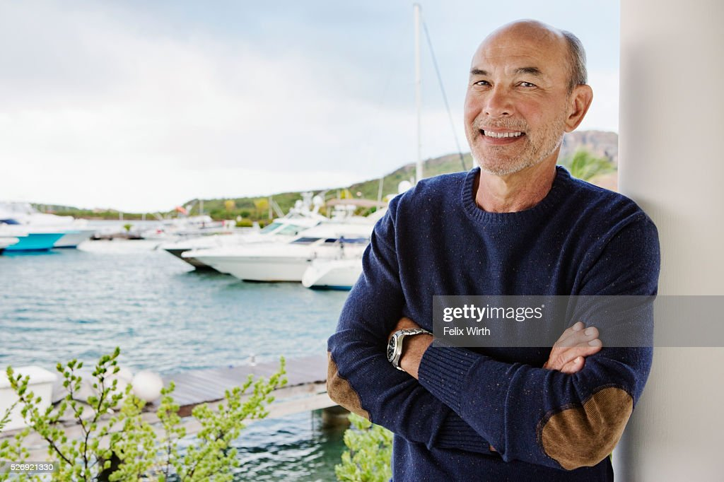 Portrait of senior man posing in front of marina : Stock Photo
